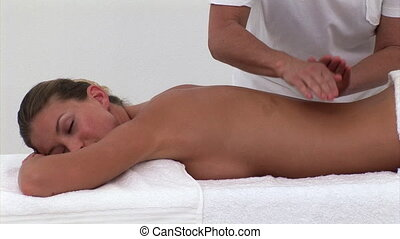 Relaxed woman enjoying a back massage in a spa center