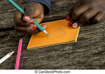 Closeup view of an African-American girl colouring a heart...