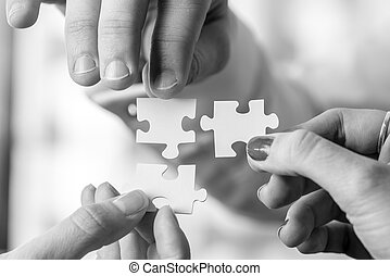 Black and white image of three people holding puzzle pieces...