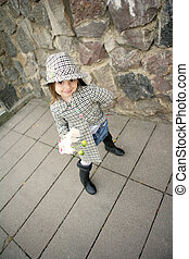 Cute girl with flower - Happy small girl wearing coat, hat...