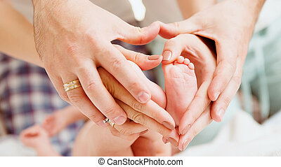 Childrens feet in hands of mother and father Feet of the...
