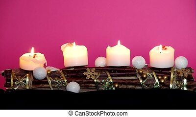 Advent wreath with white candles on a pink background