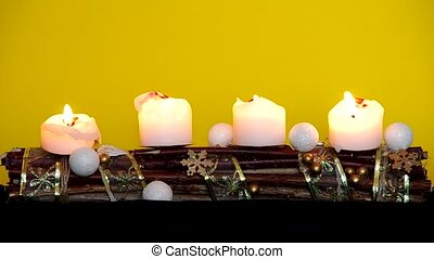 Advent wreath with white candles on a yellow background