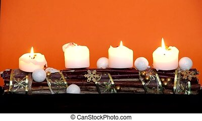 Advent wreath with white candles on a orange background