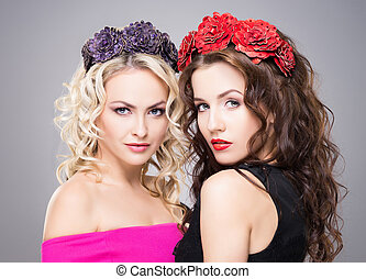 Beautiful, sensual blond and brunette wearing flower alike...