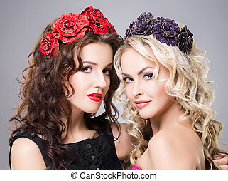 Close-up of two attractive, young ladies wearing flower...