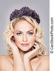 Close-up of young, sensual woman wearing purple flower alike...