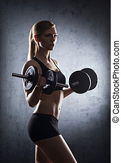 Beautiful woman training with a dumbbell in the underground...