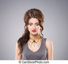 Beautiful brunette with red lipstick and luxury golden necklace witt ruby over grey background.