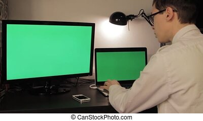 Young Man hands typing on green screen laptop computer, 2...