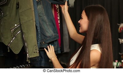 happy girl choosing new garment in fashion store