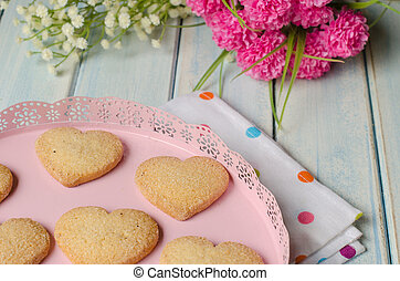 Heart-shaped butter cookies with sugar. - Pink tray with...