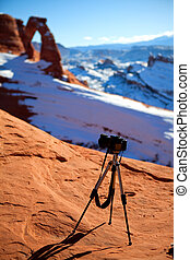 Camera at delicate arch - Camera on tripod standing with...