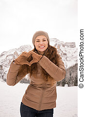 Woman showing heart shaped hands among snow-capped mountains...