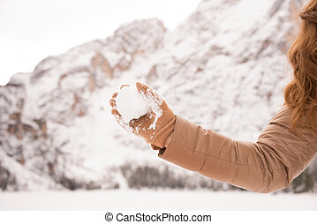Closeup on throwing snowball woman among snow-capped...