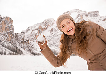 Woman outdoors among snow-capped mountains throwing snowball...