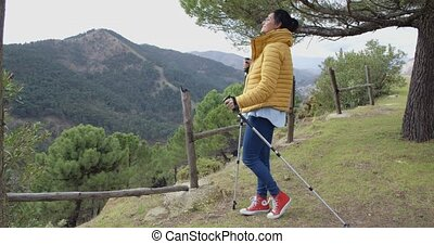Smiling hiker with poles - Smiling pretty female hiker in...