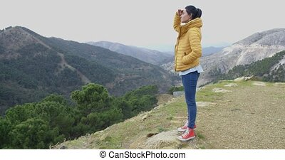 Young woman looking out over mountain scenery with her hand...