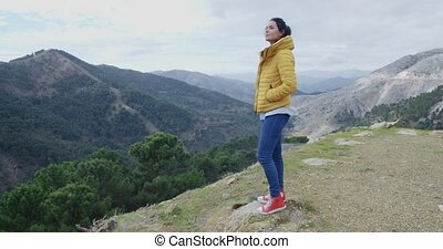 Woman in yellow coat near mountain valley - Cute young woman...