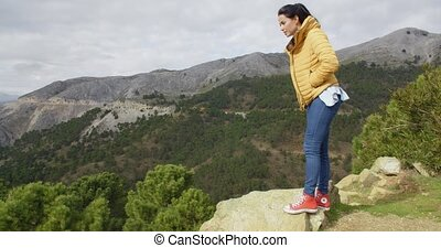 Woman in yellow coat near mountain valley