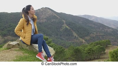 Young woman enjoying a day in nature sitting on a rock high...