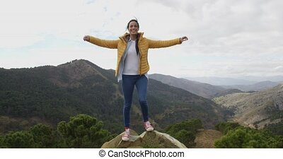 Female hiker rejoicing in the mountains standing on a high...