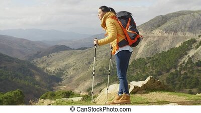 Young woman hiker standing overlooking a valley - Young...