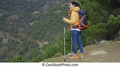 Young woman enjoying a mountain hike pausing on a plateau...