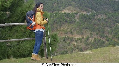 Young woman hiking on a mountain plateau with a backpack and...