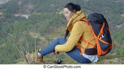 Young woman enjoying a day in the wilderness sitting on the...