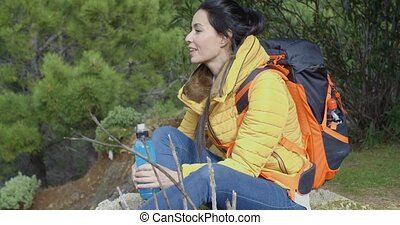 Young backpacker pausing for water - Young attractive female...