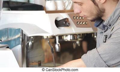Barista prepares espresso. Handsome male barista making...