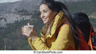 Young woman backpacker enjoying coffee as she sits...