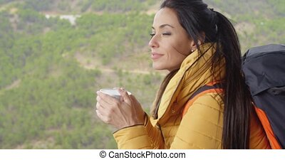 Young woman backpacker savoring her coffee - Young woman...