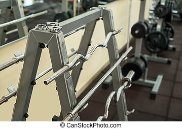 Training apparatus in gym. Barbells hanging on metal rack in...