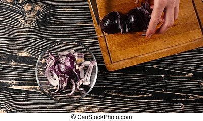 woman hands slicing onions on a wooden cutting board