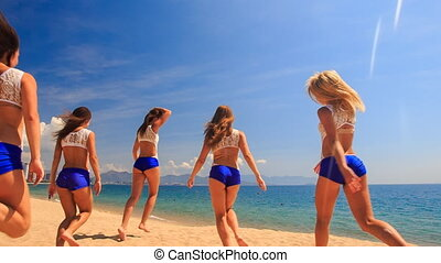 cheerleaders run out perform Scale Basket Toss on beach