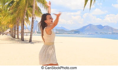 slim girl in lace frock swings with hands above on beach -...