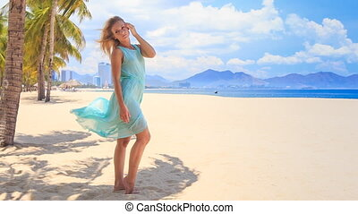 blonde girl in transparent holds hair dress under wind on...