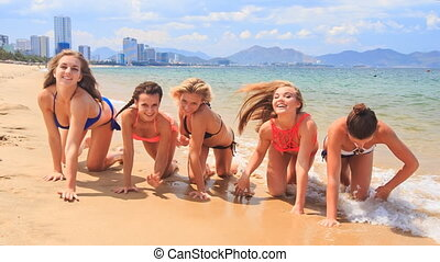 cheerleaders in bikinis crawl in line along sand beach smile...