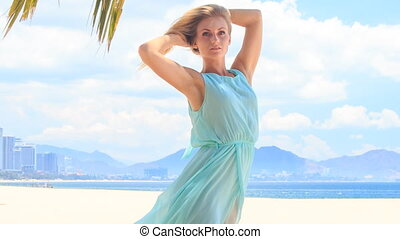 blonde girl in azure lifts hair up under wind on beach -...