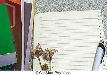 Flower pen book and a notebook on a desk