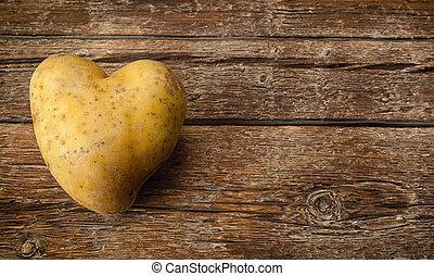 Heart Shaped Potato - Heart shaped potato on dark wooden...