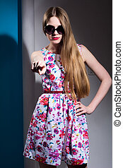 Girl in sunglasses and a dress pointing a finger at the camera