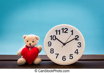 Teddy bear with pink heart and clock decoration on wooden...