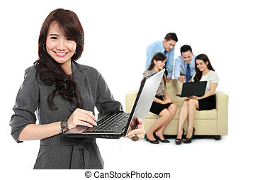 Young asian businesswoman, with her team behind holding laptop.