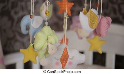 toys above baby bed - colorful toys above baby bed
