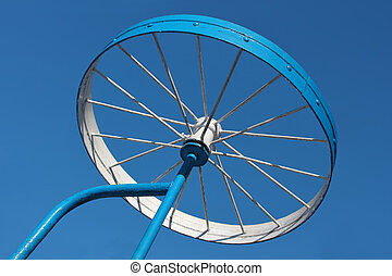 Metal detail as a bicycle wheel against the sky - Metallic...