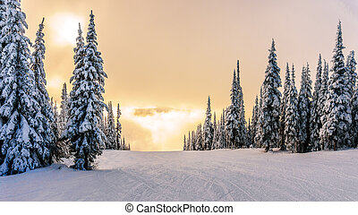 Sun breaking through the clouds on a ski hill in central...