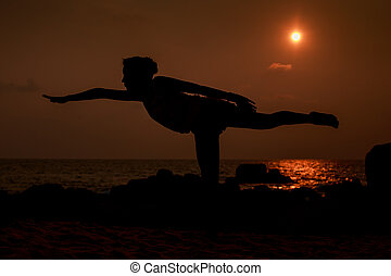 gymnast silhouette in pose leg scale against sun disk over...